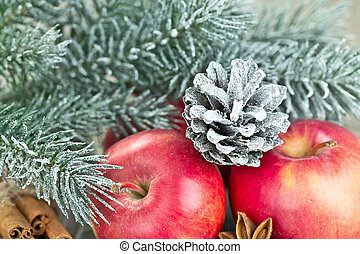Christmas red apples, snow-covered pine cone and fir...