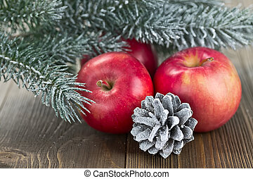 Christmas red apples, snow-covered cones and spruce twigs on...