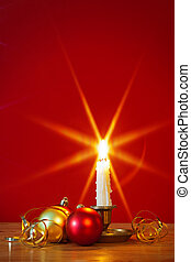 Christmas candle and decorations - A lit candle in brass...