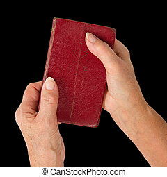 Old hands (woman) holding a very old bible, isolated on...
