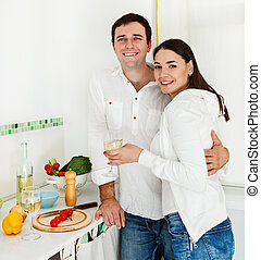 Portrait of a happy couple preparing food and drinking white...