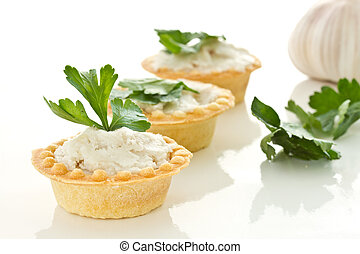tartlets with lard - tartlets with twisted bacon on a white...