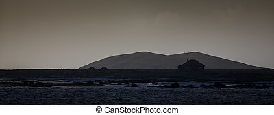 Lonely South Uist cottage next to a loch in the Outer...