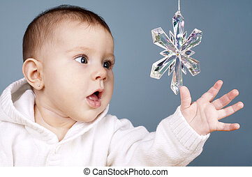 baby with snow flake - beautiful baby girl is playing with...