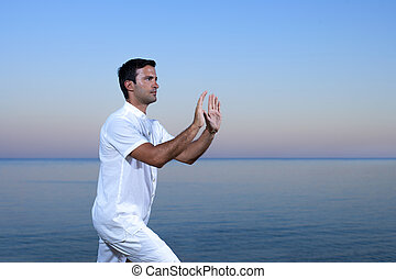 Handsome man on the beach meditating - Tai chi by the sea
