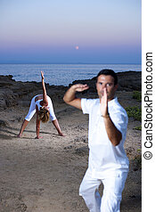 Young couple practicing yoga and Tai Chi on by the sea at...