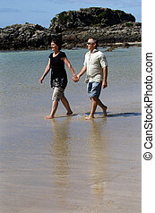 Couple during summer vacation - Young loving couple walks on...