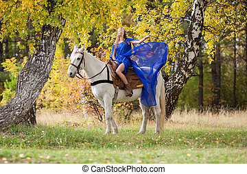 in the autumn park 3 - Young girl riding a white horse in...