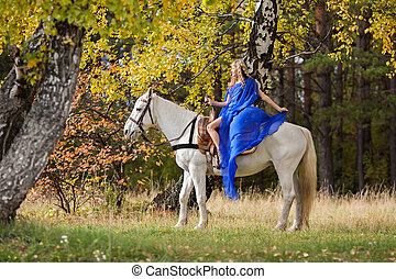 in the autumn park 4 - Young girl riding a white horse in...