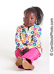 Sad with crossed arms and legs. - A young African girl being...