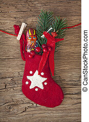 Red sock with chocolate Krampus on wooden background