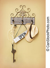 Open Sign hanging next to a key and hat