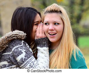 Two teen girls whispering rumours
