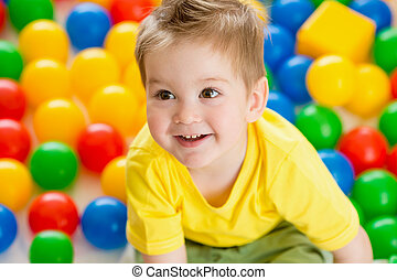 Cute kid or child playing colorful balls top view