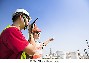 two refinery workers looking the large refinery background