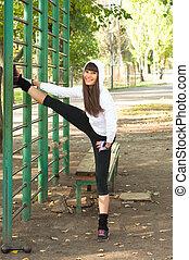 Leg stretching - Beautiful brawny young sport woman wearing...