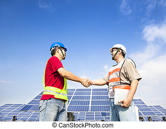 two engineers handshaking  before large solar power station