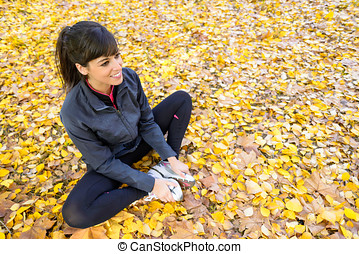 Girl stretching legs in autumn - Beautiful sporty woman...