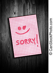 Sorry note - Sorry, handwritten reminder paper note over a...