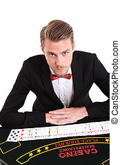 Sit down and play Blackjackdealer in a suit and bowtie White...