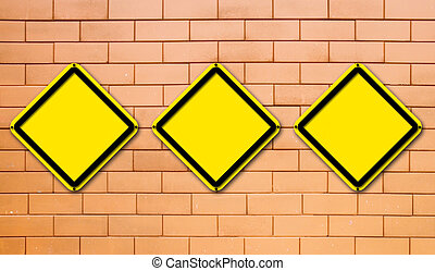 Three blank yellow traffic sign on brick wall background