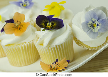 Edible flowers - close up of cupcakes decorated with...