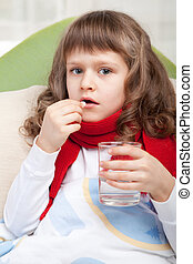 Little sick girl with scarf in bed is taking a pill -...
