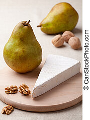 Green pears, cheese brie, cores of walnuts on wooden board