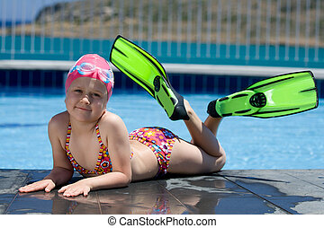 Little child in bathing cap, glasses, fins near swimming...