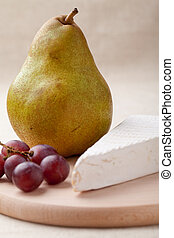Green pear, cheese brie, red grapes on wooden board macro