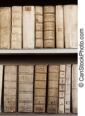 Covers of old ancient books monuscripts on shelves in...