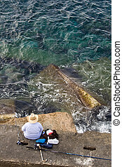 Fisherman is fishing on the sea stone, top vertical view