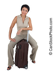 Smiling young tourist haircut woman dressed buff trouser suit sits on the  brown traveling suitcase isolated