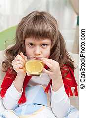 Little sick girl with scarf in bed is taking medicine -...