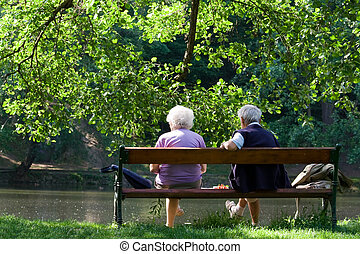 Senior couple on the bench near lake in park - Aged couple...