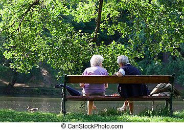 Grandparents are talking on the bench in the spring park -...