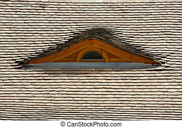 Attic window on the tilled roof