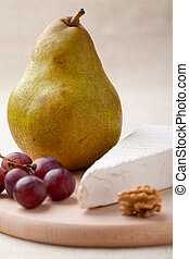 Green pear, cheese brie, walnut, grapes on wooden board macro