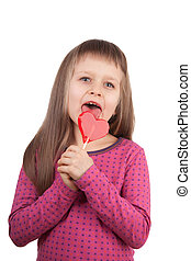 Little girl 7-8 years old licking red heart lollipop...