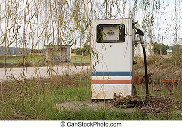 Old, rusty and abandoned gas pump against nature