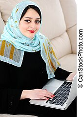 Asian Arabic young with laptop on sofa - Young woman with...