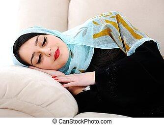 Arabic woman sleeping on sofa