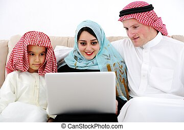 Arabic parents and little boy at home with laptop computer
