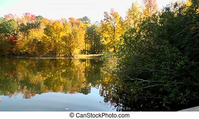 fall lake reflection - A pan across a tree lined lake ablaze...
