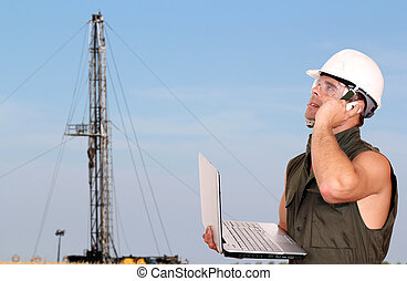 oil worker with laptop and rig
