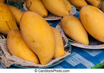 Yellow ripe mango on dish for sale in market