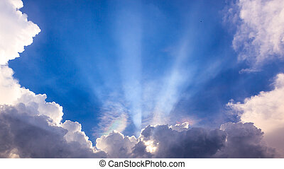 Light ray from sun behind cloud in the blue sky