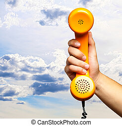Close Up Of Hand Holding Telephone against a cloudy sky...