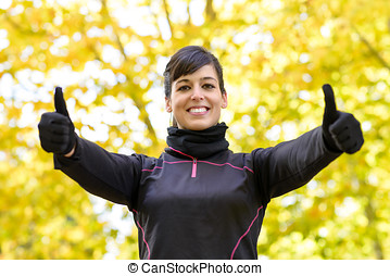 Success sportwoman with thumbs up - Cheerful brunette sport...