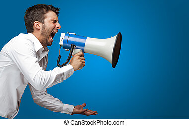 Portrait Of A Man Yelling Into A Megaphone Against Blue...